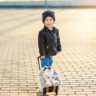 Kleines lächelndes reisendes mädchen zieht lustigen flauschigen koffer mit kaninchen zum flughafen.