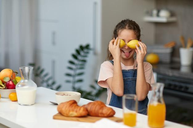 Kleines lächelndes süßes mädchen, das zitronen in der nähe von augen hält und zunge über verschwommenem küchenhintergrund zeigt. gesunder lebensstil und sauberes essenskonzept.
