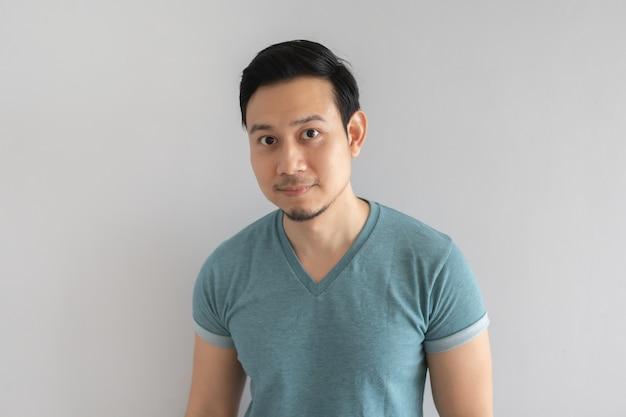 Kleines lächelngesicht des unsicheren mannes im blauen t-shirt auf grauem hintergrund.