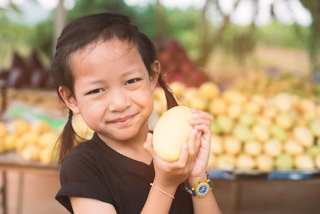 Kleines lächelnkindermädchen, das gelbe mango hält.