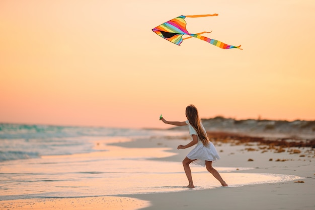 Kleines laufendes mädchen mit fliegendem drachen auf tropischem strand. kinderspiel am ufer des ozeans.