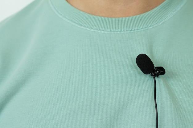 Kleines lavaliermikrofon oder mikrofonknopfloch auf der t-shirt-nahaufnahme eines mannes