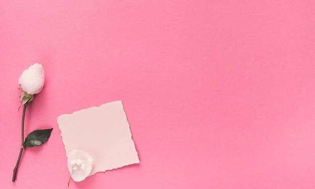 Kleines leeres papier mit weißer blume auf rosa tabelle