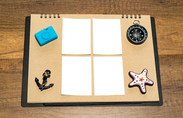 Kleines leeres weißes blatt auf braunem papier mit blauem kamera-, anker-, kompass- und sternfischmag