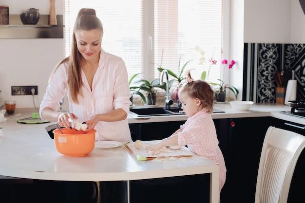 Kleines liebes kind, das elternteil mit teig an der küche hilft