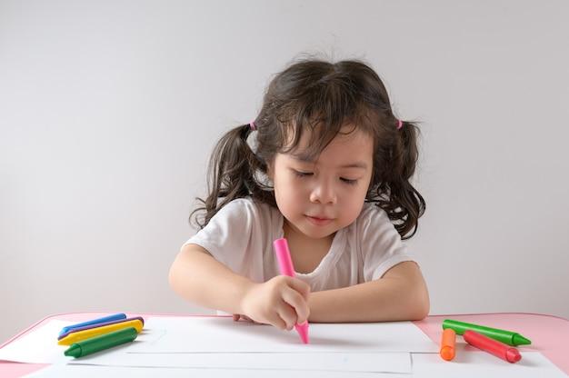 Kleines lockiges asiatisches mädchen genießt das zeichnen zu hause. bildungskonzept.