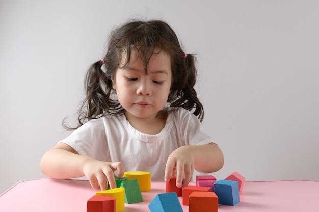 Kleines lockiges asiatisches mädchen genießt, spielzeug zu hause zu spielen. bildungskonzept.