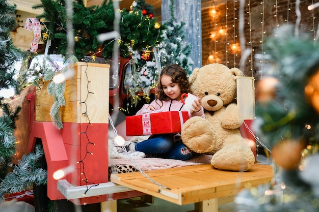 Kleines lockiges brünettes mädchen sitzt in der nähe von weihnachten und neujahr dekoriertem baum mit großem teddybär, tasse und offener roter geschenkbox