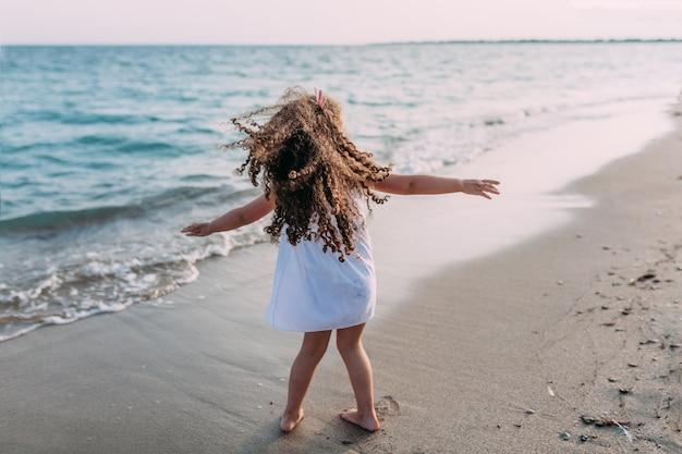 Kleines lockiges mädchen in einem weißen kleid, das auf den strand tanzt