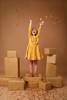 Kleines lockiges mädchen mit einem stapel von geschenken für den feiertag und goldkonfetti