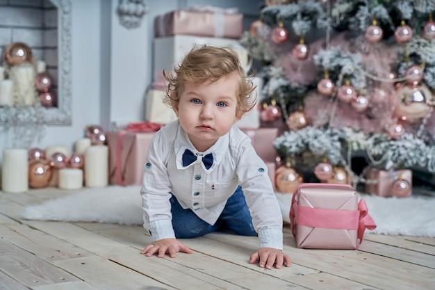 Kleines lustiges baby neben dem weihnachtsbaum.