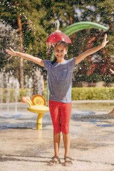 Kleines lustiges mädchen in spritzern auf wasserspielplatz im sommerpark. kinderfreuden im aquapark, wasserabenteuer