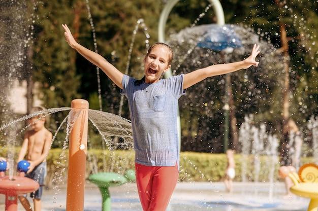 Kleines lustiges mädchen in spritzern auf wasserspielplatz im sommerpark. kinderfreuden im aquapark