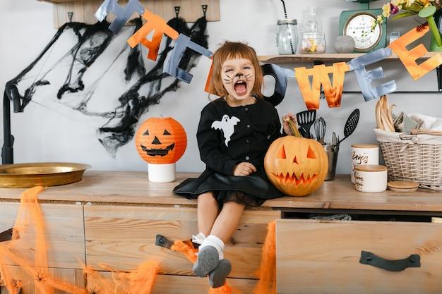 Kleines, lustiges mädchen mit einem gemalten gesicht, das auf dem hintergrund der halloween-dekorierten küche sitzt, macht jedem angst. hochwertiges foto