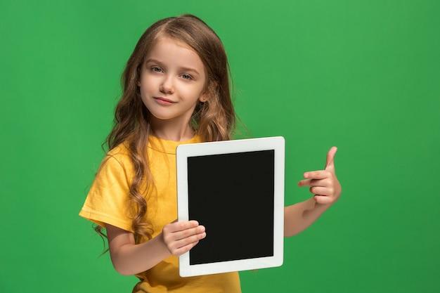 Kleines lustiges mädchen mit tablette auf grünem studio