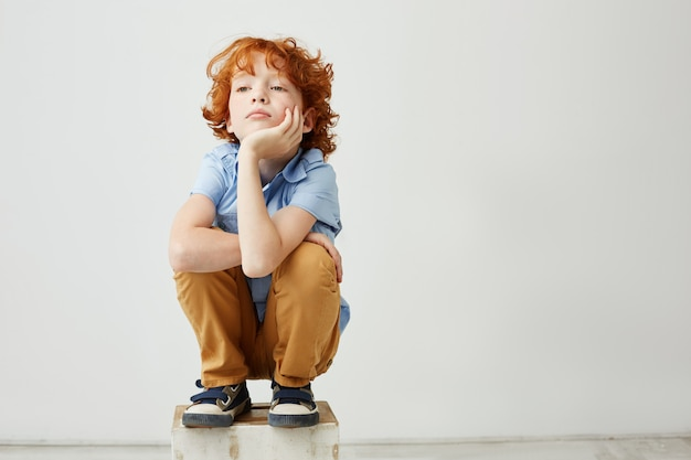 Kleines lustiges rothaariges kind sitzend, kopf mit hand haltend