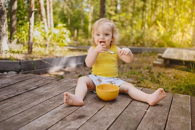 Kleines lustiges süßes blondes mädchenkindkleinkind mit schmutziger kleidung und gesicht, das babynahrungsfrucht isst oder