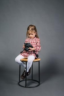 Kleines Mädchen, das auf dem Schemel betrachtet Kamera gegen grauen Hintergrund sitzt