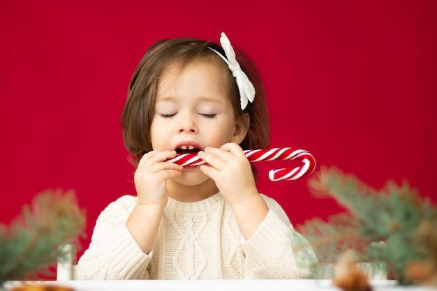 Kleines mädchen 2-4 im gestrickten kleid mit weißer schleife, die weihnachtslutscher mit geschlossenen augen auf rotem hintergrund versucht. frohe weihnachten und ein glückliches neues jahr.