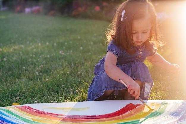 Kleines mädchen 2-4 jahre alt malt regenbogen und sonne auf einem großen blatt papier, das im sonnenlicht auf grünem rasen sitzt