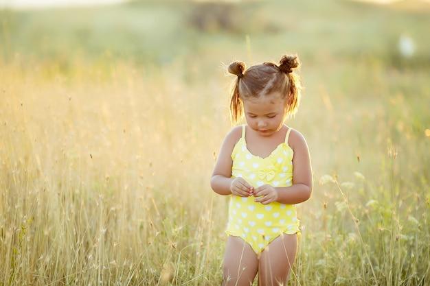 Kleines mädchen 3-5 jahre alt im sommer auf dem feld mit gelben ährchen in einem gelben badeanzug.