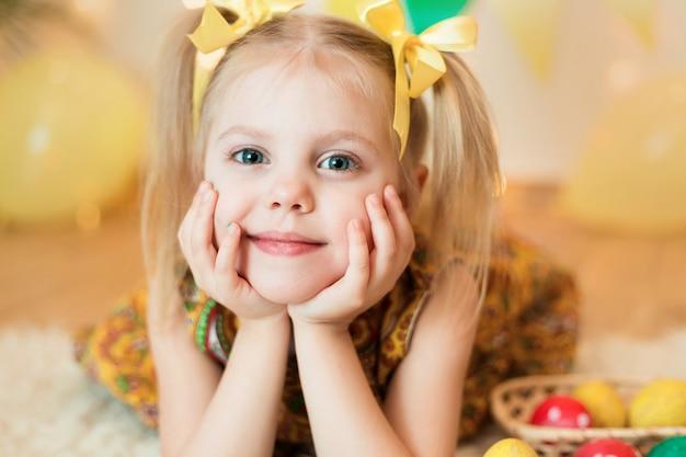 Kleines mädchen 3 jahre alt, das auf dem boden mit leuchtend gelben kleidern mit ostereiern liegt