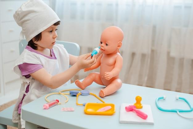 Kleines mädchen 3 jahre alte vorschüler, die doktor mit puppe spielen. das kind macht ein injektionsspielzeug.