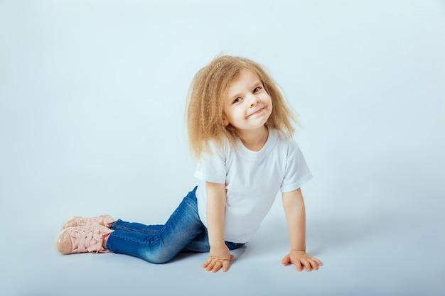 Kleines mädchen 4 jahre alt mit tragendem weißem hemd des gelockten haares, blue jeans, rosa stiefeln, die auf dem boden sitzen, lächeln und schauen