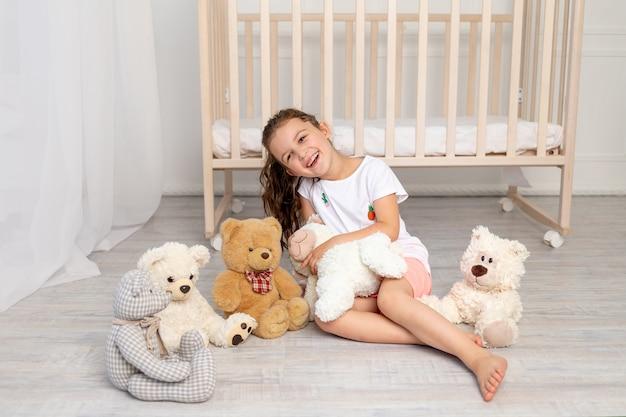 Kleines mädchen 5-6 jahre alt, das im kinderzimmer mit teddybären spielt