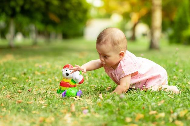 Kleines mädchen 7 monate alt, das auf einem grünen rasen in einem rosa bodysuit spielt, an der frischen luft spaziert, frühe entwicklung von kindern bis zu einem jahr