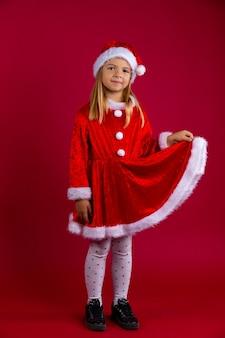 Kleines mädchen als weihnachtsmann und wintermütze verkleidet. porträt eines hübschen kleinen mädchens, das ein rotes kleid mit ihrer hand hält, lokalisiert auf roter wand.
