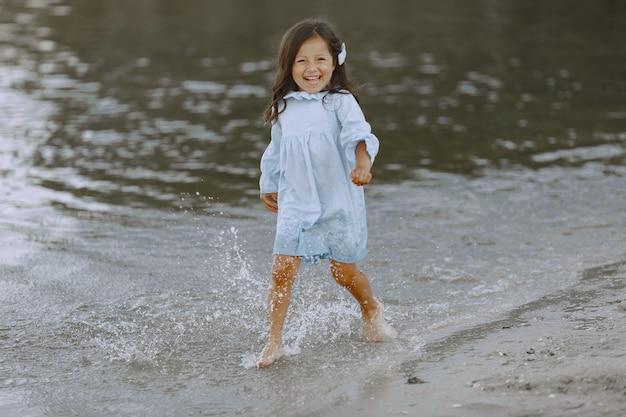 Kleines mädchen am fluss. mädchen spritzt wasser. mädchen in einem blauen kleid.
