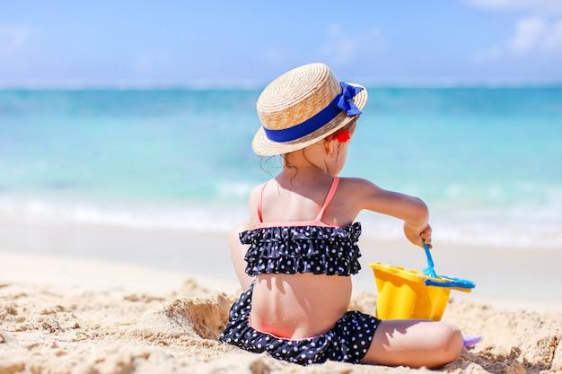 Kleines mädchen am tropischen weißen strand, der sandburg macht