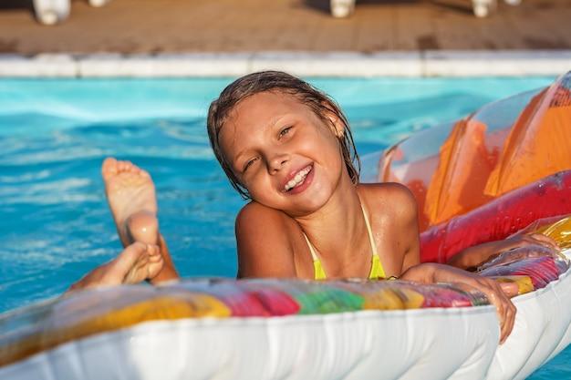 Kleines mädchen auf aufblasbarer matratze im schwimmbad. lächelndes kind, das im schwimmbad spielt und spaß hat