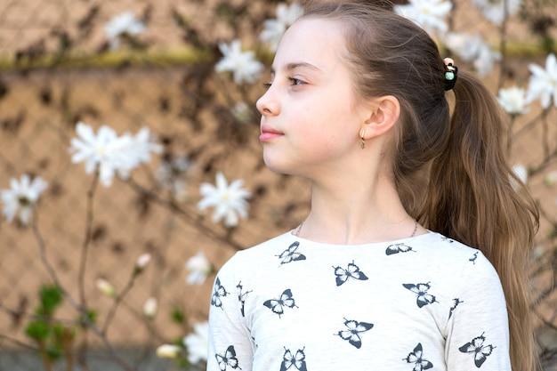 Kleines mädchen auf blumenblüte im frühjahr. kind mit blühenden blumen im freien. schönheitskind mit frischem aussehen und langen haaren. frühlings-, oster- und feiertagsfeierkonzept.