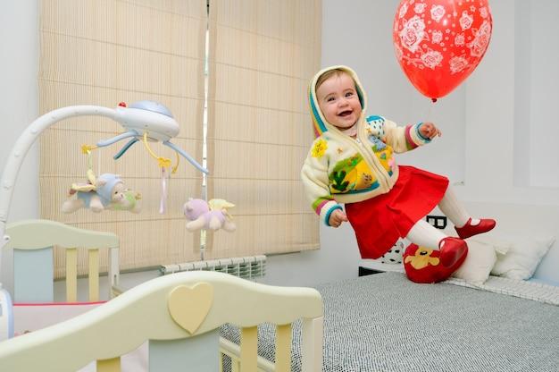 Kleines mädchen auf dem bett mit einem ballon springen