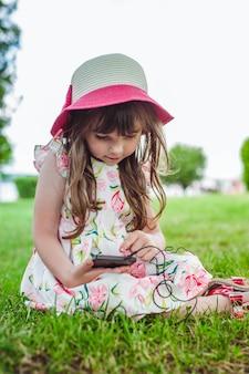 Kleines mädchen auf dem boden mit einem telefon in der hand sitzen
