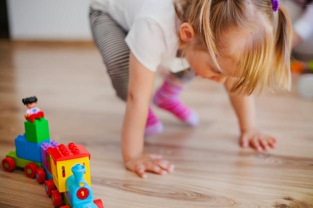 Kleines mädchen auf dem boden mit spielzeug