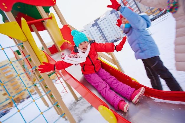 Kleines mädchen auf dem spielplatz im winter