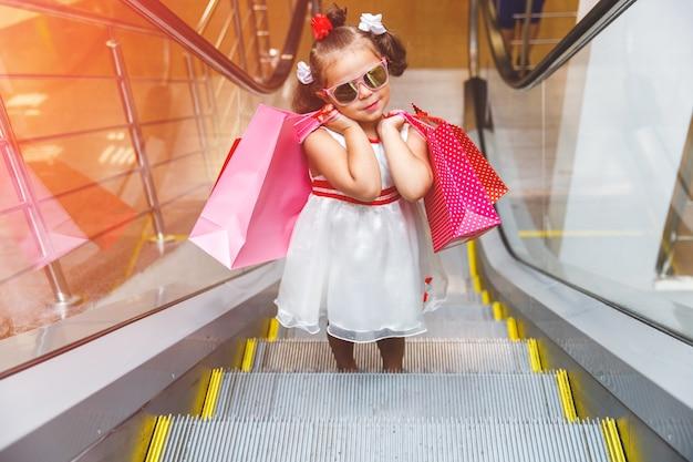 Kleines mädchen auf der rolltreppe im einkaufszentrum mit einkäufen