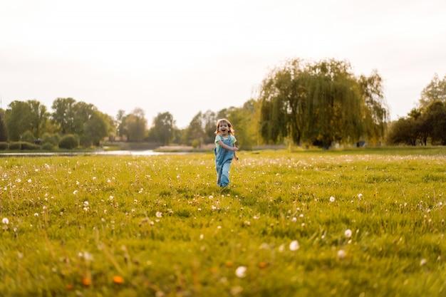 Kleines mädchen auf einem löwenzahnfeld, am sonnenuntergang, emotionales glückliches kind.