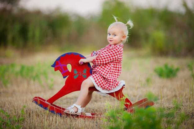 Kleines mädchen auf einem spielzeugpferd spazieren im sommer