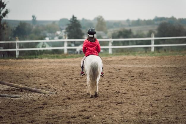 Kleines mädchen auf einem weißen pony