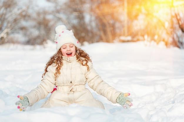 Kleines mädchen auf einem winterweg am sonnigen tag.