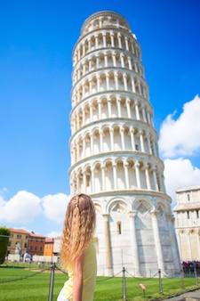 Kleines mädchen auf italienischen ferien nahe dem berühmten lehnenden turm von pisa, italien