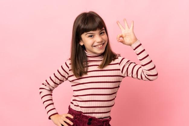 Kleines mädchen auf rosa hintergrund isoliert, das mit den fingern ein ok-zeichen zeigt