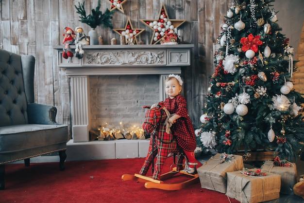 Kleines mädchen auf schaukelpferd im weihnachtlich geschmückten raum