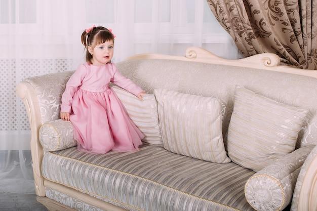 Kleines mädchen auf sofa zu hause im rosa kleid. kindheitskonzept