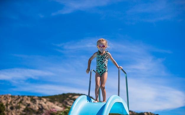 Kleines mädchen auf wasserrutsche am aquapark an den sommerferien