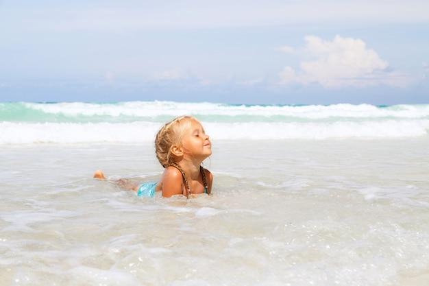 Kleines mädchen badet im meer am strand mit weißem sand